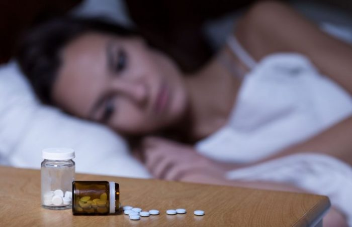 woman lying on bed with sleeping pills on side table