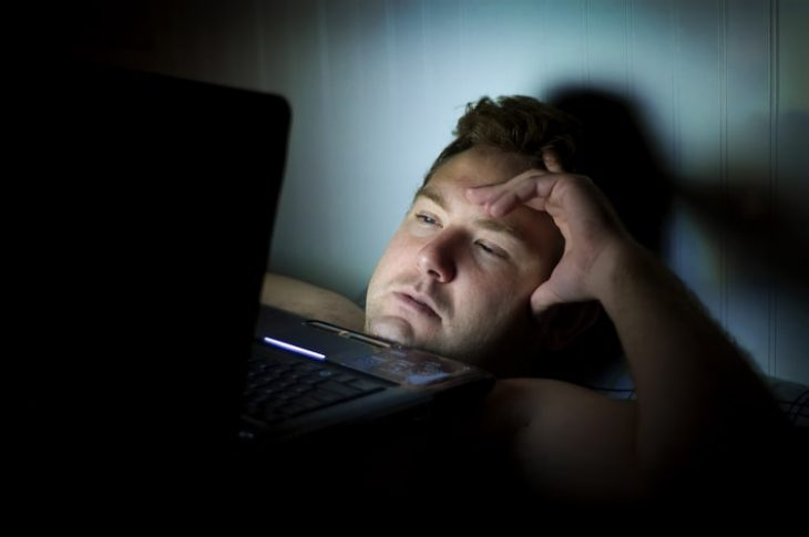 man working on laptop in dark