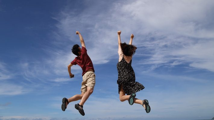 Happy man and woman jumping with joy