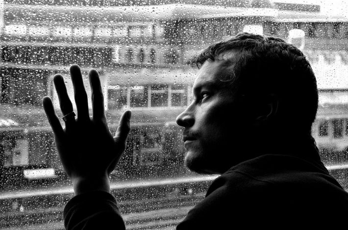 Depressed man looking out the window
